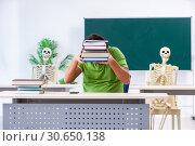 Купить «Funny male student in the classroom with skeleton», фото № 30650138, снято 26 февраля 2019 г. (c) Elnur / Фотобанк Лори