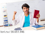 Купить «Young student chemist in the classroom», фото № 30651946, снято 9 октября 2018 г. (c) Elnur / Фотобанк Лори