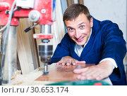 portrait of man in uniform working with electrical screwdriver on plywood indoors. Стоковое фото, фотограф Яков Филимонов / Фотобанк Лори