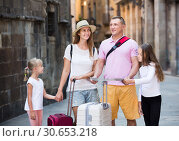 Купить «Cheerful family visiting sights with map», фото № 30653218, снято 25 мая 2019 г. (c) Яков Филимонов / Фотобанк Лори