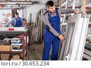 Купить «Laborer is inspecting the window frame», фото № 30653234, снято 30 марта 2017 г. (c) Яков Филимонов / Фотобанк Лори
