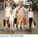 Купить «Man and woman with children walking and holding bags», фото № 30653342, снято 13 августа 2017 г. (c) Яков Филимонов / Фотобанк Лори