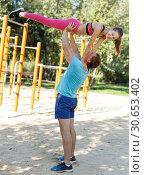 Купить «Man with daughter doing acrobatic elements», фото № 30653402, снято 29 сентября 2018 г. (c) Яков Филимонов / Фотобанк Лори