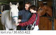 Купить «Portrait of couple standing at stable», фото № 30653422, снято 26 ноября 2018 г. (c) Яков Филимонов / Фотобанк Лори