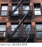 Купить «Low angle view of fire escape on apartment building, Lower Manhattan, New York City, New York State, USA», фото № 30653878, снято 13 декабря 2019 г. (c) Ingram Publishing / Фотобанк Лори