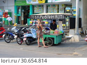 Купить «Tourist buys food from a street vendor pancakes in Thailand», фото № 30654814, снято 26 марта 2019 г. (c) Григорий Писоцкий / Фотобанк Лори