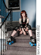 Roller derby girl sitting on stairs. Стоковое фото, фотограф sumners / easy Fotostock / Фотобанк Лори