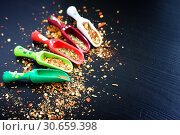 Купить «Spices and wooden spoons on black background», фото № 30659398, снято 13 апреля 2019 г. (c) Papoyan Irina / Фотобанк Лори