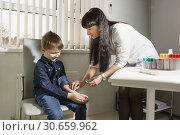 Медсестра протирает руку мальчика, чтобы провести тест Манту, направленный на выявление наличия специфического иммунного ответа на введение туберкулина. Профилактика и ранняя диагностика. Стоковое фото, фотограф Наталья Гармашева / Фотобанк Лори
