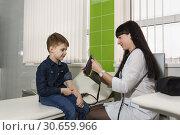 Купить «Медицинский работник готовит тонометр для измерения артериального давления мальчику. Ребенок смотрит с интересом», фото № 30659966, снято 17 марта 2019 г. (c) Наталья Гармашева / Фотобанк Лори