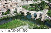 Купить «Aerial view of historic centre of Besalu with Romanesque bridge over Fluvia river, Catalonia, Spain», видеоролик № 30664490, снято 12 июня 2018 г. (c) Яков Филимонов / Фотобанк Лори