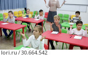 Купить «Portrait of smiling smart school children sitting with hands raised during lesson with female teacher in classroom», видеоролик № 30664542, снято 30 января 2019 г. (c) Яков Филимонов / Фотобанк Лори