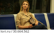Купить «Young woman with a smartphone and headphones enters a subway car», видеоролик № 30664562, снято 31 марта 2019 г. (c) Яков Филимонов / Фотобанк Лори