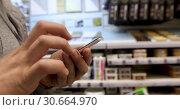 Купить «Man stand use phone hold ham in hardware store», видеоролик № 30664970, снято 27 апреля 2019 г. (c) Ekaterina Demidova / Фотобанк Лори