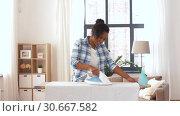Купить «african american woman ironing bed linen at home», видеоролик № 30667582, снято 15 апреля 2019 г. (c) Syda Productions / Фотобанк Лори