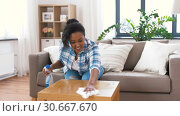 Купить «african american woman cleaning table at home», видеоролик № 30667670, снято 15 апреля 2019 г. (c) Syda Productions / Фотобанк Лори