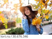 Купить «Beautiful young woman holding a bunch of autumn leaves», фото № 30676346, снято 21 октября 2018 г. (c) Happy Letters / Фотобанк Лори