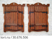 Two windows on the white wall. Orenburg, Russia - April, 14, 2019: Two windows with platbands and wooden shutters. Стоковое фото, фотограф Вадим Орлов / Фотобанк Лори