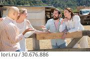 Купить «Friends chatting near wooden fencing», фото № 30676886, снято 11 апреля 2019 г. (c) Яков Филимонов / Фотобанк Лори