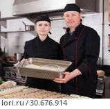 Купить «Two cooks holding baking tray with cannelloni», фото № 30676914, снято 11 апреля 2019 г. (c) Яков Филимонов / Фотобанк Лори