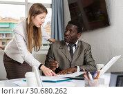 Купить «Young woman assistant having conversation with man boss during work», фото № 30680262, снято 18 июля 2019 г. (c) Яков Филимонов / Фотобанк Лори