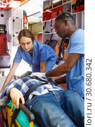 Купить «Emergency doctors providing first aid to man in ambulance auto», фото № 30680342, снято 30 ноября 2018 г. (c) Яков Филимонов / Фотобанк Лори