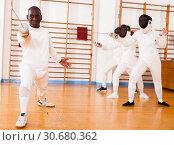 Купить «Sporty african american man fencer practicing effective fencing techniques», фото № 30680362, снято 11 июля 2018 г. (c) Яков Филимонов / Фотобанк Лори