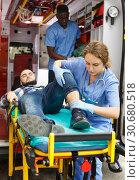 Купить «Ambulance team providing medical care to patient», фото № 30680518, снято 30 ноября 2018 г. (c) Яков Филимонов / Фотобанк Лори