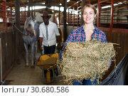 Купить «Two workers spreading hay at stable», фото № 30680586, снято 2 октября 2018 г. (c) Яков Филимонов / Фотобанк Лори