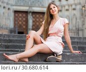 Купить «young female in rose dress sitting in city», фото № 30680614, снято 26 августа 2017 г. (c) Яков Филимонов / Фотобанк Лори