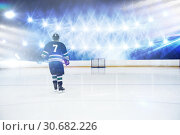 Composite image of rear view of player holding ice hockey stick. Стоковое фото, агентство Wavebreak Media / Фотобанк Лори