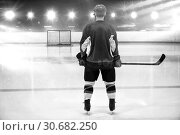 Composite image of rear view of hockey player at ice rink. Стоковое фото, агентство Wavebreak Media / Фотобанк Лори