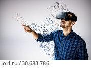 Купить «Composite image of businessman looking though virtual reality simulator against white background», фото № 30683786, снято 26 мая 2019 г. (c) Wavebreak Media / Фотобанк Лори