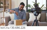 Купить «video blogger opening parcel box at home», видеоролик № 30686226, снято 30 апреля 2019 г. (c) Syda Productions / Фотобанк Лори