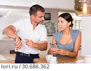 Купить «Irritated husband pointing at wristwatch to wife with phone», фото № 30686362, снято 17 июля 2018 г. (c) Яков Филимонов / Фотобанк Лори