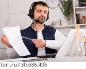 Купить «Young man call centre operator with headphones working», фото № 30686406, снято 25 декабря 2017 г. (c) Яков Филимонов / Фотобанк Лори