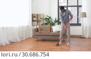 Купить «man with broom cleaning floor at home», видеоролик № 30686754, снято 26 апреля 2019 г. (c) Syda Productions / Фотобанк Лори