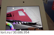 Купить «Exhibition visitor choosing the color of future trains on a tablet with a touch screen», видеоролик № 30686954, снято 16 апреля 2019 г. (c) Антон Гвоздиков / Фотобанк Лори