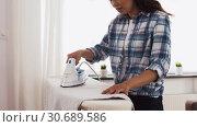 Купить «asian woman ironing bed linen at home», видеоролик № 30689586, снято 25 апреля 2019 г. (c) Syda Productions / Фотобанк Лори