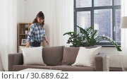Купить «asian woman arranging sofa cushions at home», видеоролик № 30689622, снято 25 апреля 2019 г. (c) Syda Productions / Фотобанк Лори
