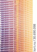 Купить «New unfinished skyscraper building under construction closup», фото № 30690098, снято 24 апреля 2018 г. (c) Сергей Новиков / Фотобанк Лори