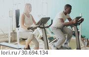 Купить «African man and Caucasian woman exercising on stationary bikes at gym», видеоролик № 30694134, снято 24 марта 2019 г. (c) Яков Филимонов / Фотобанк Лори