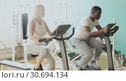 African man and Caucasian woman exercising on stationary bikes at gym. Стоковое видео, видеограф Яков Филимонов / Фотобанк Лори