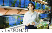 Купить «Portrait of confident woman standing arms crossed in pet store on background of colored fish tanks», видеоролик № 30694138, снято 26 марта 2019 г. (c) Яков Филимонов / Фотобанк Лори