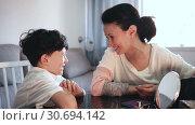 Купить «Cheerful woman telling funny story to her teenage son at home table», видеоролик № 30694142, снято 26 апреля 2019 г. (c) Яков Филимонов / Фотобанк Лори