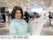 Купить «The Woman chooses blouse in the store», фото № 30694582, снято 1 мая 2019 г. (c) Володина Ольга / Фотобанк Лори