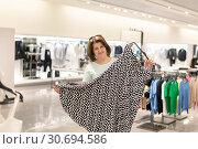 Купить «The Woman chooses skirt in the store», фото № 30694586, снято 1 мая 2019 г. (c) Володина Ольга / Фотобанк Лори