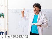 Купить «Young student chemist in the classroom», фото № 30695142, снято 9 октября 2018 г. (c) Elnur / Фотобанк Лори