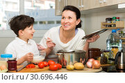 Купить «Woman and her son preparing food», фото № 30696446, снято 28 марта 2019 г. (c) Яков Филимонов / Фотобанк Лори