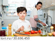 Купить «Boy preparing food with mother», фото № 30696450, снято 28 марта 2019 г. (c) Яков Филимонов / Фотобанк Лори